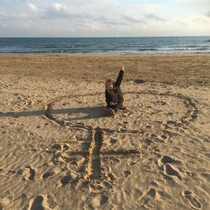 Vila i sitt ritade hon-tecken i stranden. Min dotter.