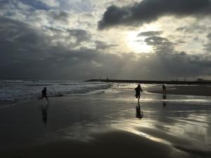 Barnen springer på stranden